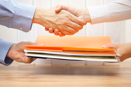 a handshake with an exchange of paper files
